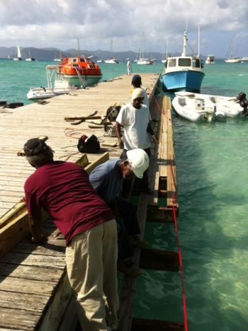 Men at work during the dock repair exercise at Great Harbour. Photo: VINO team of reporters