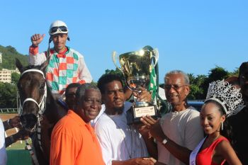 Jahmal Rivera of Jo-Dinga Stables receives the coveted Premier's Cup from Premier Dr. the Hon. D. Orlando Smith following the win today, August 6, 2013. At right is newly crowned Miss British Virgin Islands, Rosanna Chichester. Photo: VINO