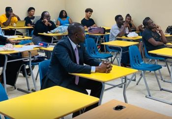 Hon Kye M. Rymer sitting amongst students in the classroom watching the presentation of the Premier. Photo: Facebook