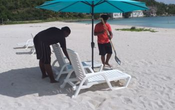 Shaquon George and Ernest Jacob assisting with the setting up of beach chairs ahead of the opening ceremony of D-Tan Spot. Photo: Team of Reporters