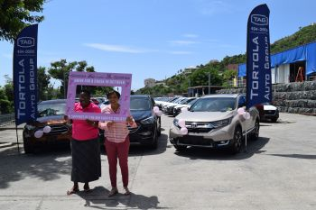 President of the BVI Cancer Society, Gloria Fahie (left) with TAG's Managing Director, Patricia Romney stand in front some of the Ford, Honda and Hyundai models featured in TAG's 'Drive for a Cause' promotion in October to support the fight against cancer. Photo: TAG