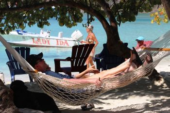 A man relaxes under the shade of a tree in a hammock at Jost Van Dyke near Foxy's Tamarind Bar. Photo: VINO
