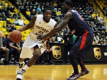 Southern Miss forward Norville Carey drives to the basket against South Alabama's Tafari Whittingham in college basketball action in November 2014 at Reed Green Coliseum. Photo: Eric J. Shelton/Hattiesburg American