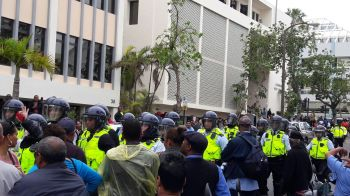 Riot police face off with Bermudian protesters on December 2, 2016. Photo: Provided