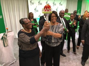 Ms Naomi Turnbull passing the VIP torch on to Reverend Edris O'Neal. Photo: Team of Reporters