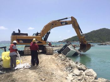 Calvin Smith aka 'Duck', the driver of a heavy duty truck servicing the Cruise Pier Development Project worksite today October 6, 2014 misjudged his manoeuvre causing the vehicle to topple sideways into the water. Photo: Team of Reporters